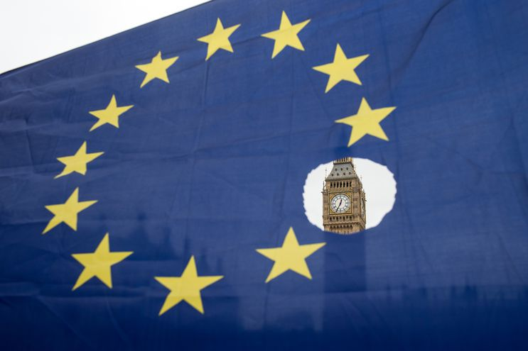 (FILES) In this file photo taken on March 29, 2017 A pro-remain protester holds up an EU flag with one of the stars symbolically cut out in front of the Houses of Parliament shortly after British Prime Minister Theresa May announced to the House of Commons that Article 50 had been triggered in London on March 29, 2017. - The UK and European Union will on December 30 sign a mammoth trade pact to put the seal on their drawn-out Brexit divorce in the dwindling hours before they part ways definitively at the dawning of 2021. (Photo by OLI SCARFF / AFP)