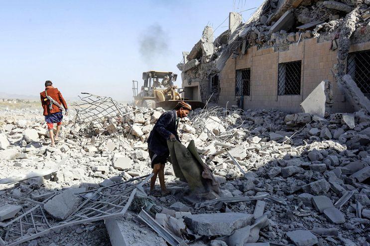 Dos personas inspeccionan los escombros del centro de detención destruído, al sur de Saná.