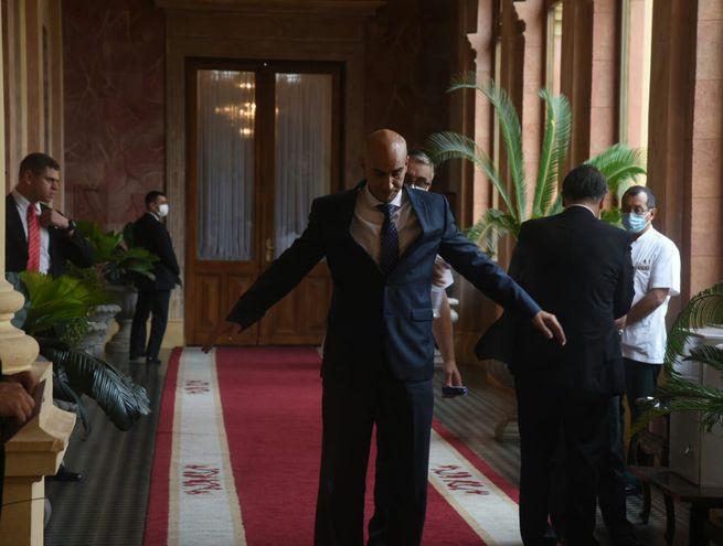 Un funcionario del Palacio de Gobierno desinfecta al ministro de Salud, Julio Mazzoleni, a su llegada al edificio.