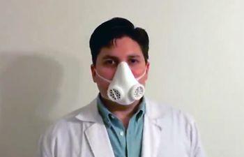 El médico mostrando una de las mascarillas de bioseguridad.