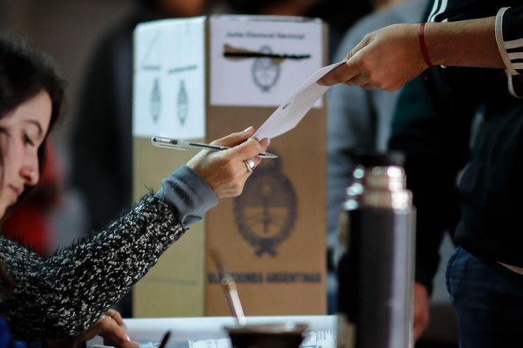 Un hombre recibe su papeleta electoral este domingo en Buenos Aires.