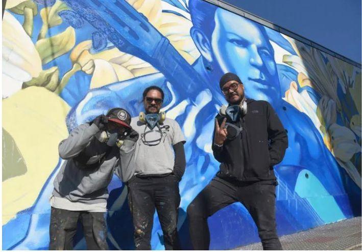 Los artistas frente al mural inaugura sobre la calle Montevideo.
