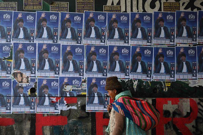 Una mujer camina frente a un muro con propaganda electoral del presidente boliviano Evo Morales.