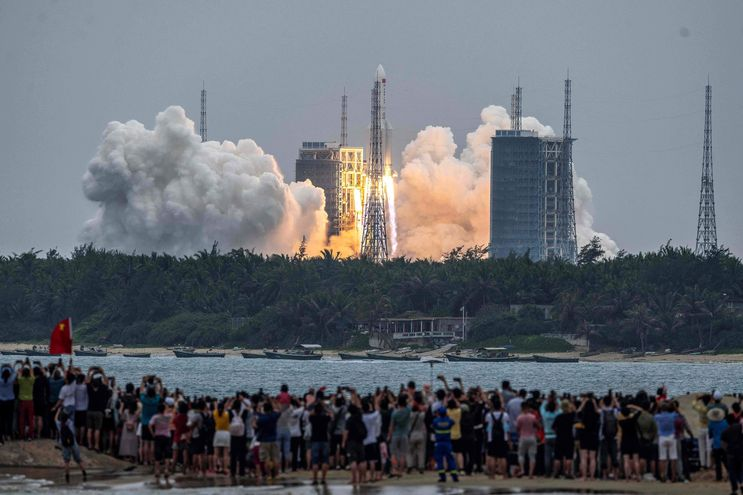 """(FILES) In this file photo taken on April 29, 2021 People watch a Long March 5B rocket, carrying China's Tianhe space station core module, as it lifts off from the Wenchang Space Launch Center in southern China's Hainan province. - The Pentagon said Wednesday it is following the trajectory of a Chinese rocket expected to make an uncontrolled entry into the atmosphere this weekend, with the risk of crashing down in an inhabited area.  US Secretary of Defense Lloyd Austin is """"aware and he knows the space command is tracking, literally tracking this rocket debris,"""" Pentagon spokesman John Kirby said. (Photo by STR / AFP) / China OUT"""