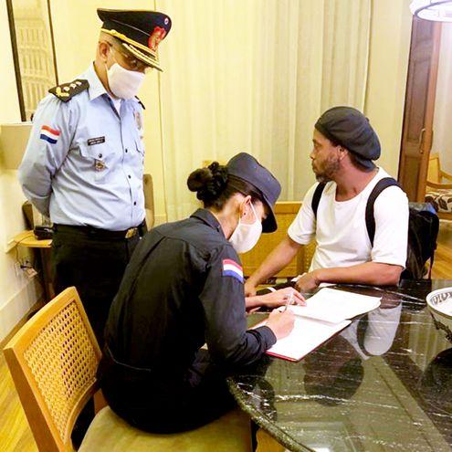 Una agente policial labra acta en la suite de Ronaldinho. Observa el comisario principal Carlos Miguel López Russo, jefe de la comisaría 3ª de Asunción.