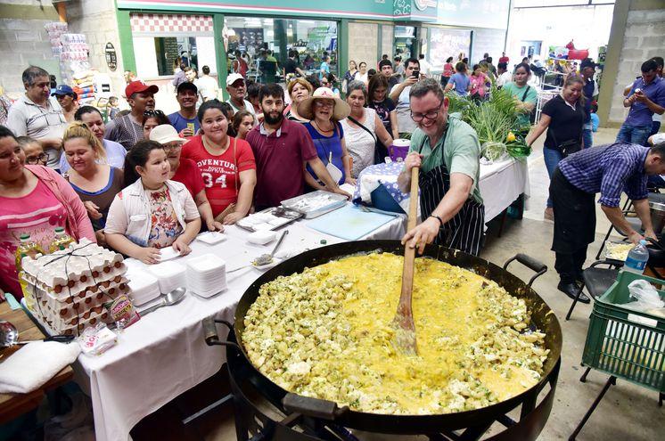 Con 70 Kg de mandioca, 25 Kg de queso, 21 litros  de aceite, 60 mazos de cebollita y 300 huevos, Rodolfo Angenscheidt preparó mandio'o chyryry y pastel mandi'o  que los clientes del mercado  degustaron gratuitamente.