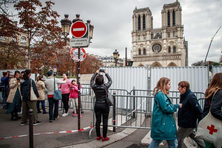 Turistas toman fotografías de la zona de obras frente a la catedral de Notre Dame en París.