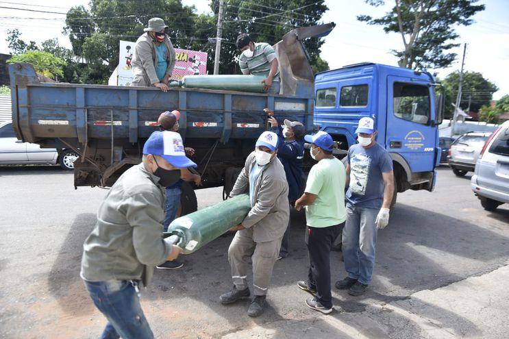 Funcionarios municipales bajan balones de oxígeno de un camión en el Hospital de Villa Elisa.