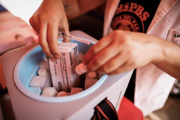 AME5015. ASUNCIÓN (PARAGUAY), 04/05/2021.- Personal médico toma un frasco de la vacuna Astrazeneca hoy, en la sede de la Secretaría Nacional de Deportes de Paraguay, en Asunción (Paraguay). Paraguay prosiguió este martes su campaña de vacunación a personas de 75 años en adelante sin descartar rebajar la edad en los próximos días para alcanzar a más franjas de la población, mientras el Ministerio de Salud hace frente a unos 500 casos de posibles aplicaciones irregulares de dosis contra la Covid-19. EFE/ Nathalia Aguilar