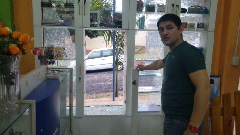 Benjamín Cantero, dueño del local asaltado, muestra el vidrio roto por los delincuentes.