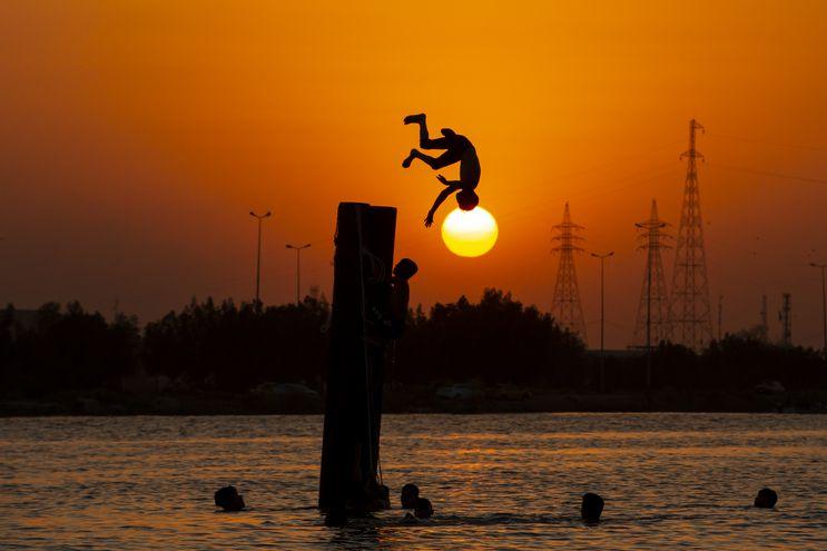 Un niño salta a las aguas del río Shatt Al-Arab, en la ciudad de Basra, Irak.