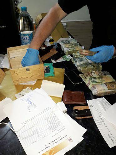 Un agente de la Policía efectúa el recuento de los billetes, tanto en guaraníes, como en dólares encontrados en una de las celdas.