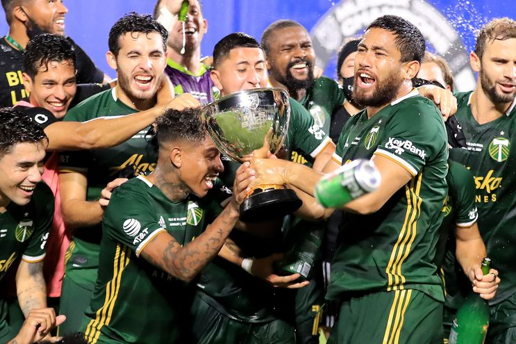 REUNION, FLORIDA - AUGUST 11: Andy Polo #7 (L) and Bill Tuiloma #25 of Portland Timbers celebrate with the MLS Is Back champions trophy after the final match of MLS Is Back Tournament between Portland Timbers and Orlando City at ESPN Wide World of Sports Complex on August 11, 2020 in Reunion, Florida.   Sam Greenwood/Getty Images/AFP == FOR NEWSPAPERS, INTERNET, TELCOS & TELEVISION USE ONLY ==